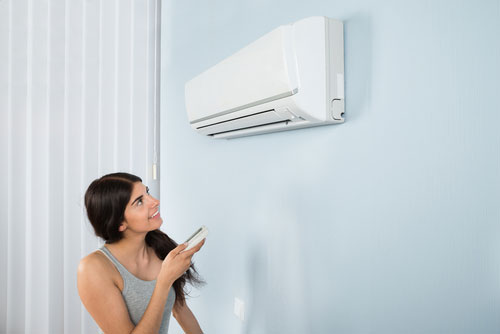 young woman turning on ac